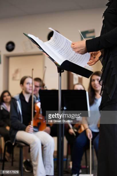 Teacher holding sheet music in class