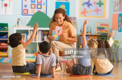 Teacher holding up different flash card in classroom, children (4-7) raising hands : Stock Photo