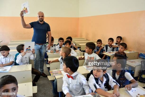 A teacher holds up a book as Iraqi children attend the first day of class at the 'AlZeitun Primary Boys' School' after the school reopened in the...