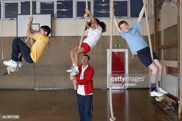 Teacher in a Gym Helping School Boys and Girls Climb Ropes