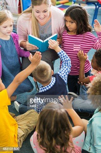 Insegnante in classe con un gruppo di bambini in età prescolastica multirazziale
