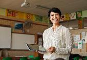 Teacher in classroom holding tablet