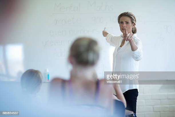Teacher in classroom talking at whiteboard