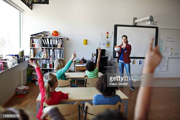 Teacher in front of a class of raised hands