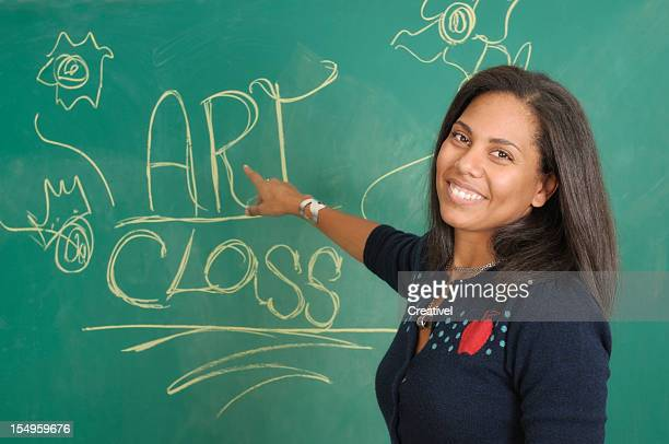 Teacher  in front of blackboard, art class