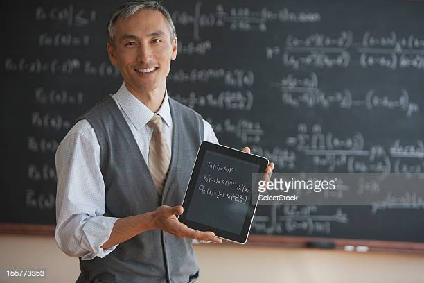 Teacher in front of blackboard with electronic tablet