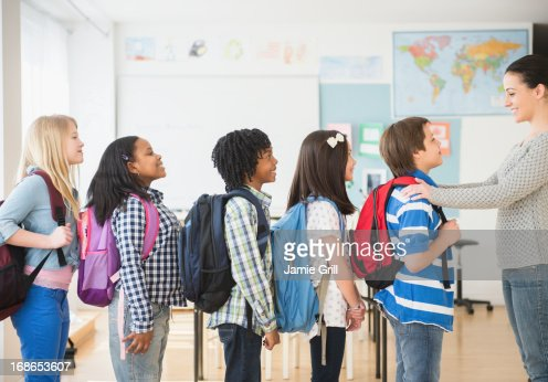 Teacher In Front Row Students In Classroom Stock
