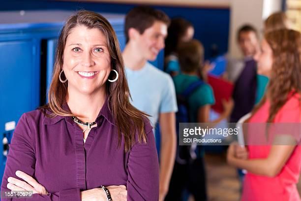 Teacher in front of students at school locker area