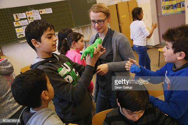 Teacher Ina Orbitz leads pupils at the 'Welcome Class' for immigrant children including children of migrants and refugees at the LeoLionniSchule...