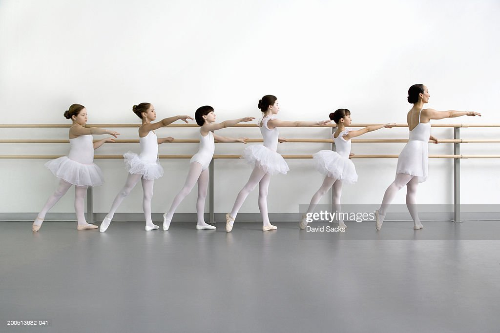Teacher leading pupils (9-13) at bar in ballet class, side view