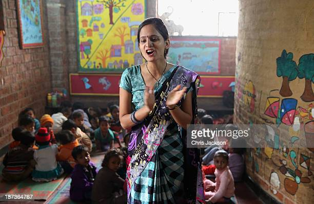 A teacher leads a lesson at Katha Community School in the Govindpuri slum district during day 3 of an official visit to India on November 8 2013 in...