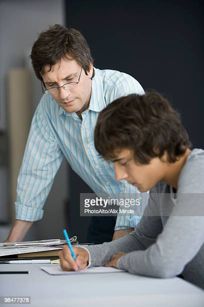 Teacher leaning on desk assisting student in classroom