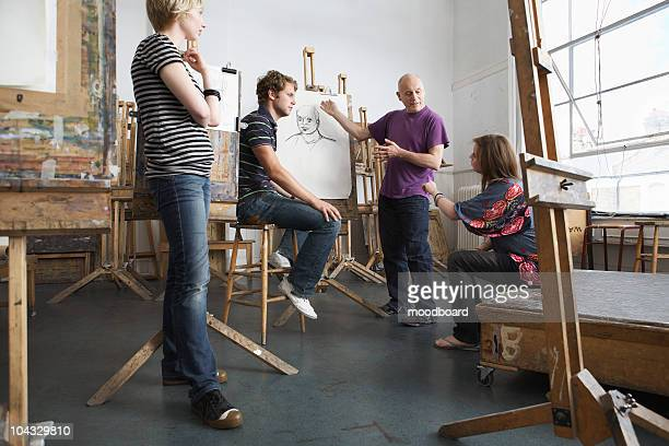 Teacher lecturing  students at art school