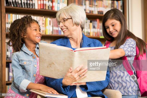 Teacher, librarian reads book to elementary students in library or classroom.
