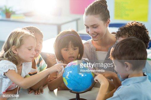 Teacher looking at schoolchildren touching globe : Stock Photo