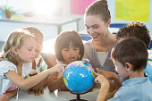 Smiling female teacher looking at schoolchildren touching globe in classroom