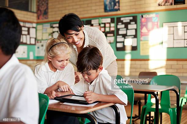 Teacher looking at tablet with kids