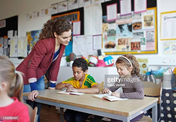 Teacher looking in book with children