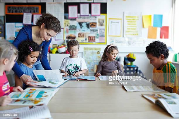 Teacher looking in books with children