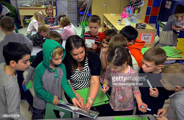 Teacher Maggie Gearing reads to a group of her students at Golden Pond School a private preschool on Friday February 28 in Ashburn VA Kindergartener...