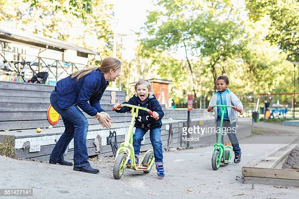 Teacher motivating children on push scooters during race
