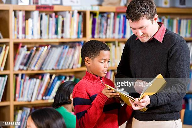 Teacher or librarian helping African American boy in library