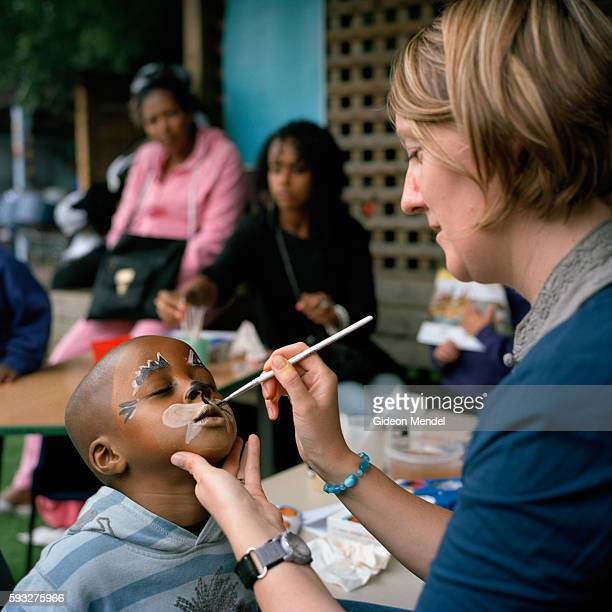 A teacher paints the face of a pupil at Kingsmead Primary School during a school festival The school primarily serves children who live on the...