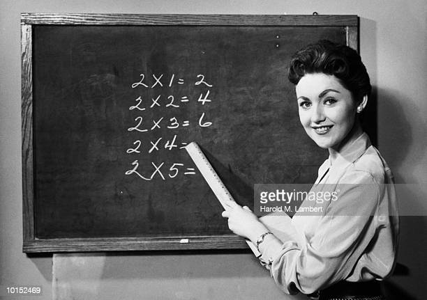 Teacher pointing to blackboard (B&W)