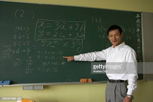 Teacher pointing to equation on blackboard, smiling
