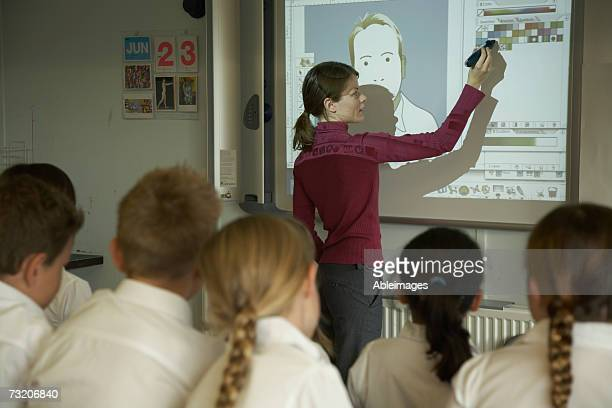 Teacher pointing to video screen to students (8-10) in classroom, rear view