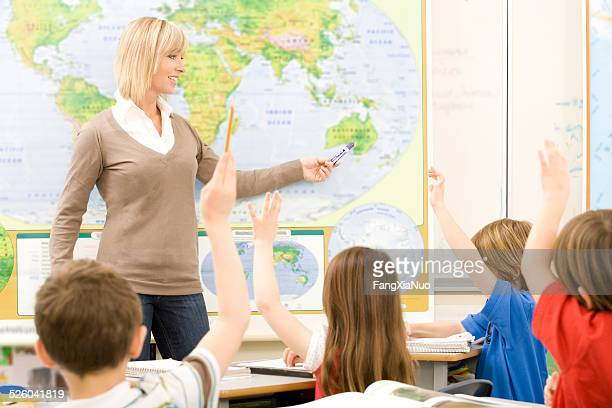 Teacher Points To A Map Of The World