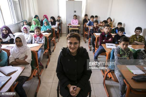A teacher poses for a photo during a class at a temporary school in Reyhanli district of Hatay Turkey on November 16 2017 Turkish and Syrian teachers...