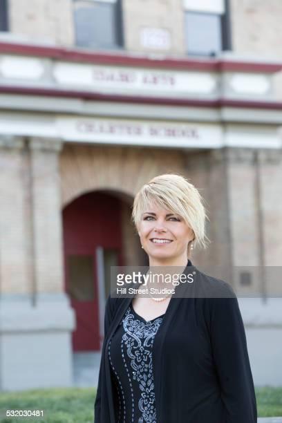 Teacher posing outside high school