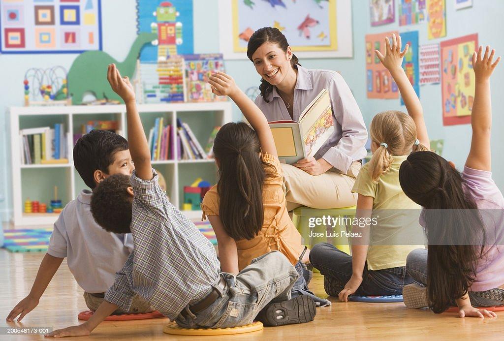 Teacher reading book in classroom, children (2-7) raising hands : Stock Photo