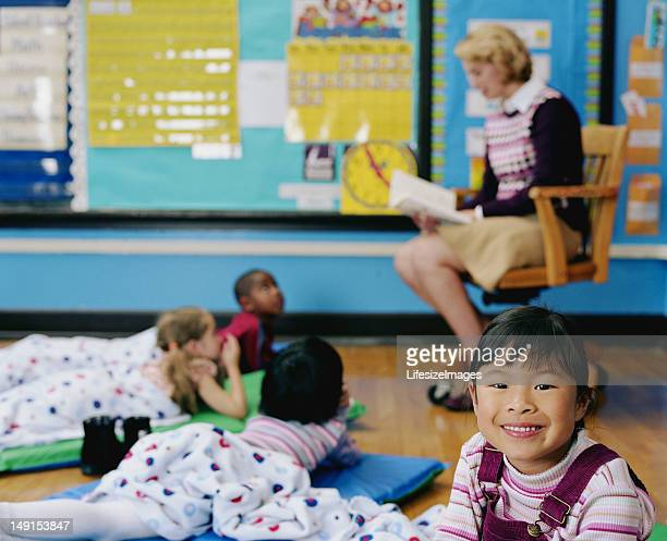 Teacher reading book to students (4-6) (focus on girl smiling)