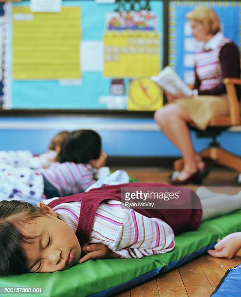 Teacher reading book to students (4-6) (focus on girl napping)