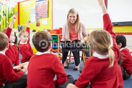 Teacher Reading Story To Elementary School Pupils : Stock Photo