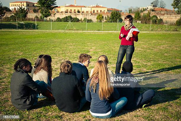 Teacher Reading to her students on lawn