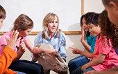 Science class - teacher (30s) showing animal skull (giraffe) to group of elementary school children.