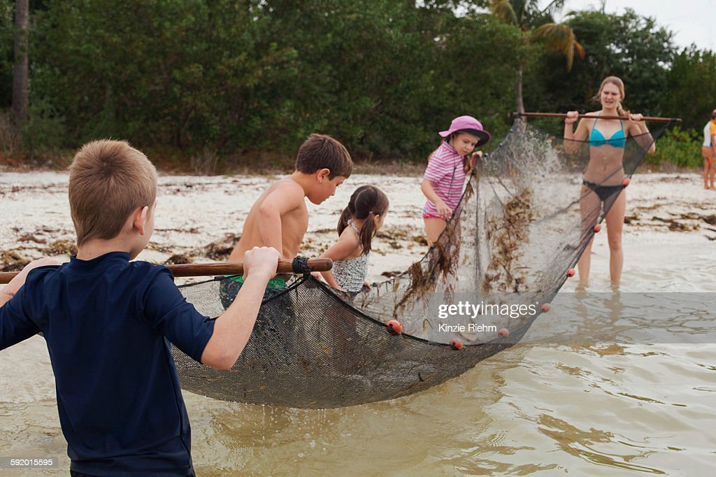 Teacher showing children how to use traditional fish net for Sjfc fish r net
