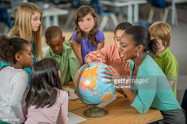 Teacher Showing Students Places on a World Globe