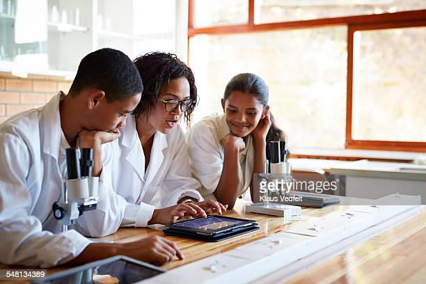 Teacher showing students science project on tablet