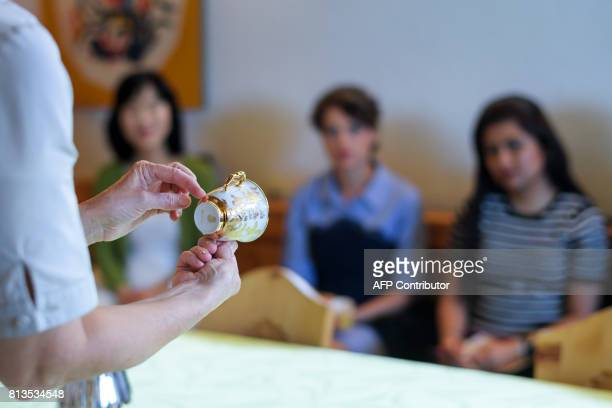 A teacher shows a cup during a lesson at the Switzerland's last finishing school Institut Villa Pierrefeu on June 26 2017 in Glion Eight women sit...
