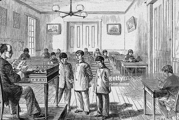 A teacher sits at a desk on raised platform and points to a student who recites a lesson at Chinese College Hartford Connecticut late 1870s The...