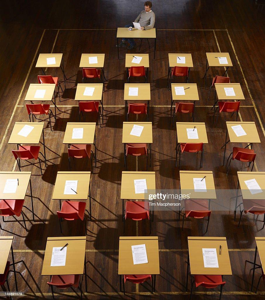 teacher sits in exam hall : Stock Photo