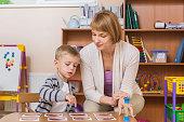 Teacher sitting and teaching student in preschool