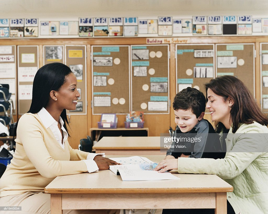 Teacher Sitting at a School Desk Showing a Book to a Parent and Her Son : Stock Photo