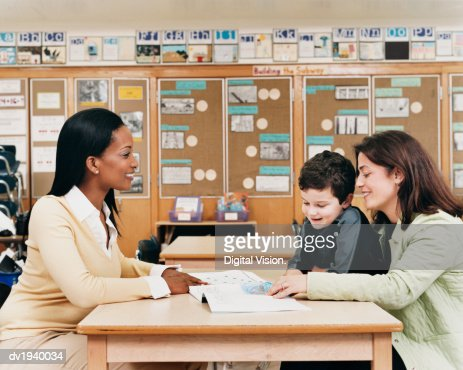 Teacher Sitting at a School Desk Showing a Book to a Parent and Her Son : Foto stock