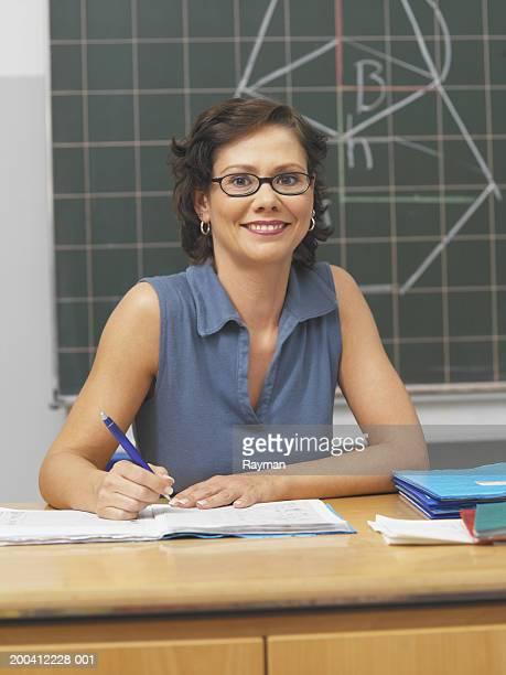 Teacher sitting at desk holding pen, smiling, portrait