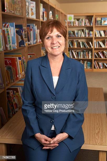Teacher sitting on table in school library, portrait